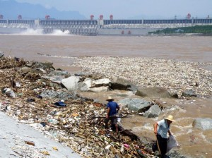This image shows the Three Gorges Dam in the background with masses of waste floating and being washed up on the shore of the Yangtze River in the foreground.